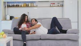 Unga par som kopplar av i deras lägenhet, ligger på soffan och håller ögonen på filmen lager videofilmer