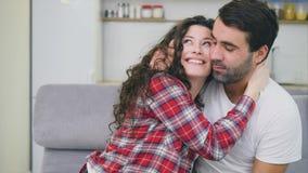 Unga par som kopplar av i deras lägenhet och att sitta på soffan, hållande ögonen på TV Vänner och lycklig kram stock video