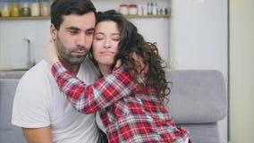 Unga par som kopplar av i deras lägenhet och att sitta på soffan, hållande ögonen på TV Vänner och lycklig kram Se rak in i stock video