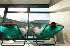 Unga par som kopplar av i wellnessbrunnsort Royaltyfri Foto
