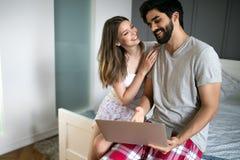 Unga par som kopplar av p? s?ng med b?rbara datorn F?r?lskelse, teknologi, lycka, folk och roligt begrepp fotografering för bildbyråer