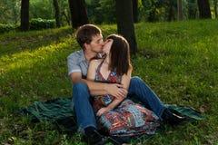 Unga par som kysser på en romantisk picknick royaltyfria bilder