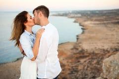 Unga par som kysser på, vaggar med den spektakulära sikten på bakgrunden arkivfoton