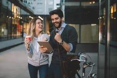 Unga par som ler och anv?nder teknologi i stad royaltyfri foto