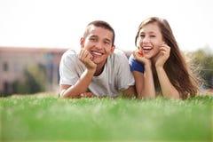 Unga par som ligger på gräs Royaltyfri Bild