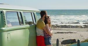 Unga par som omfamnar nära skåpbilen på en solig dag 4k lager videofilmer