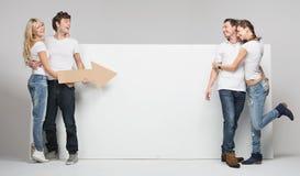 Unga par som pekar en andra par Arkivfoto