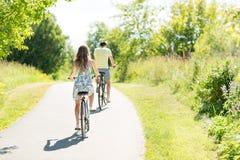 Unga par som rider cyklar i sommar arkivbild