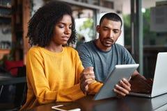 Unga par som ser den digitala minnestavlan i kafé royaltyfria bilder