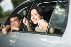 Unga par som sitter i den nya bilen Royaltyfri Foto