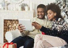 Unga par som sitter i jul dekorerat rum och använder tabellen royaltyfri bild