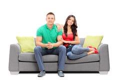 Unga par som sitter på en sofa Fotografering för Bildbyråer