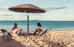 Unga par som sitter på en tropisk sandig strand under paraplyet royaltyfri bild