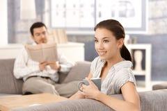 Unga par som sitter på hemmastatt le för sofa fotografering för bildbyråer