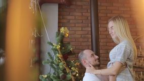 Unga par som sitter på säng på bakgrunden av julgranen Festlig hemafton En man kysser en kvinna arkivfilmer