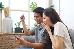 Unga par som sitter på soffan, håller ögonen på mobiltelefonen och känner sig surprise&happy royaltyfria bilder