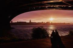 Unga par som sitter under en bro under solnedgång i Mainz arkivfoton