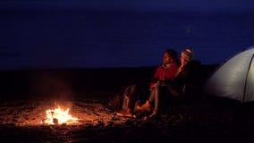 Unga par som sitter vid branden Campa med t?lt vid havet Landskap i ett bergigt omr?de arkivfilmer