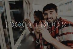 Unga par som slås in i pläd Äta för matlastbil arkivfoton