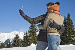 Unga par som tar foto på snowen royaltyfri bild