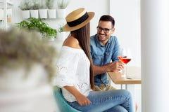 Unga par som tycker om exponeringsglas av vin i deras favorit- kafé royaltyfri bild