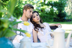Unga par som tycker om kaffe i trädgården Arkivfoton