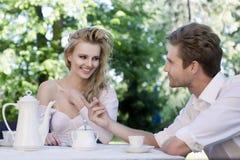 Unga par som tycker om lunch i trädgården Arkivfoto