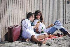 Unga par som tycker om picknicken på stranden Royaltyfri Foto