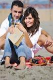 Unga par som tycker om picknicken på stranden Royaltyfria Foton