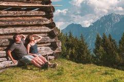 Unga par som tycker om sikt av österrikiska fjällängar royaltyfri foto