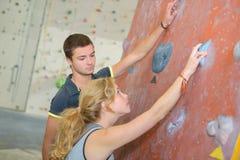 Unga par stod vid den inomhus klättraväggen arkivbilder