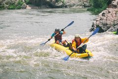 Unga par tycker om vitt vatten som kayaking p? floden arkivbilder