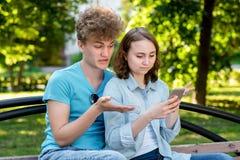 unga pardeltagare En grabb med en flickasommar parkerar i natur De sitter på en bänk i stad I händer rymmer a royaltyfri fotografi