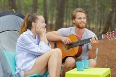 Unga parturister som har gyckel som spelar gitarren, i att campa arkivbilder