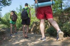 Unga pojkar för fotvandrareflickaslut med ryggsäcken Trekking tillsammans Aktiva fotvandrare Royaltyfri Bild