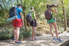 Unga pojkar för fotvandrareflickaslut med ryggsäcken Trekking tillsammans Aktiva fotvandrare Royaltyfri Fotografi
