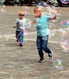 Unga pojkar jagar såpbubblor och fångar dem arkivbilder