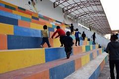 Unga pojkar klättrar över stadionmomenten på deras väghem från ettskola program i Cuzco, Peru arkivfoton