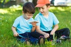 Unga pojkar med den trådlösa smartphonen och minnestavlan royaltyfri bild