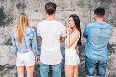 Unga pojkar och flickor står framsidan till den gråa väggen Endast en flicka har vänt tillbaka på kamera Den kinesiska flickan är Royaltyfri Foto