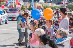Unga pojkar räcker ut fester till familjer som håller ögonen på Williams Lake Stampede Parade arkivfoton