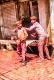 Unga pojkar som besprutar folk med målarfärgfärg på den Holi festivalen Arkivbild