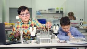 Unga pojkar som gör kemi, biologi experimenterar i skolalaboratorium arkivfilmer