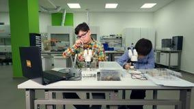 Unga pojkar som gör kemi, biologi experimenterar i skolalaboratorium lager videofilmer