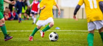 Unga pojkar som sparkar fotbollfotboll på sportfältet Arkivfoto