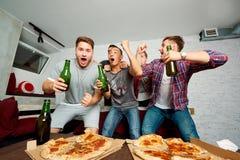 Unga pojke-fans håller ögonen på TV, kopplar av, har gyckel och dricker öl vän Royaltyfri Foto