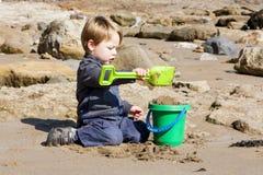 Unga pojkebyggnadssandslottar på stranden Royaltyfri Fotografi