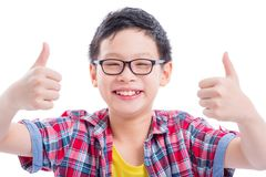Unga pojkevisningtummar up och leenden över vit arkivfoto