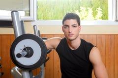 unga posera weigths för bodybuildingidrottshallman Arkivfoto