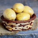 unga potatisar Hel ung potatis i en vide- korg på tappningen trätabell closeup Arkivfoton